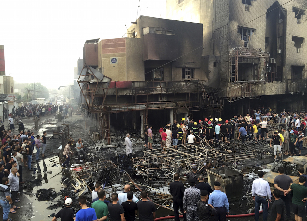 Iraqi security forces looking for victims as civilians gather at the site after a car bomb at a commercial area in Karada neighborhood, Baghdad, Iraq, Sunday, July 3, 2016. Bombs went off early Sunday in two crowded commercial areas in Baghdad. (AP Photo/Khalid Mohammed)